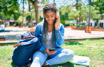 Young african american student woman smiling happy listening to music sitting on the grass.