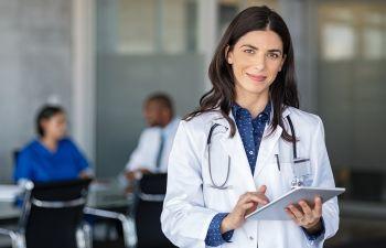 Confident female doctor using digital tablet.