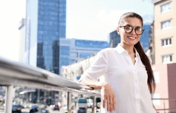 Businesswoman with glasses on a city street.
