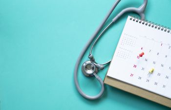 Stethoscope and calendar on the green background.