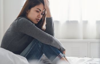 Asian young woman sitting on the bed feeling depressed.