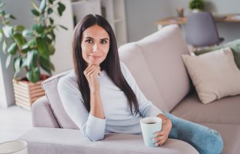 Relaxed dark-haired woman with a cup of coffee sitting on the sofa.