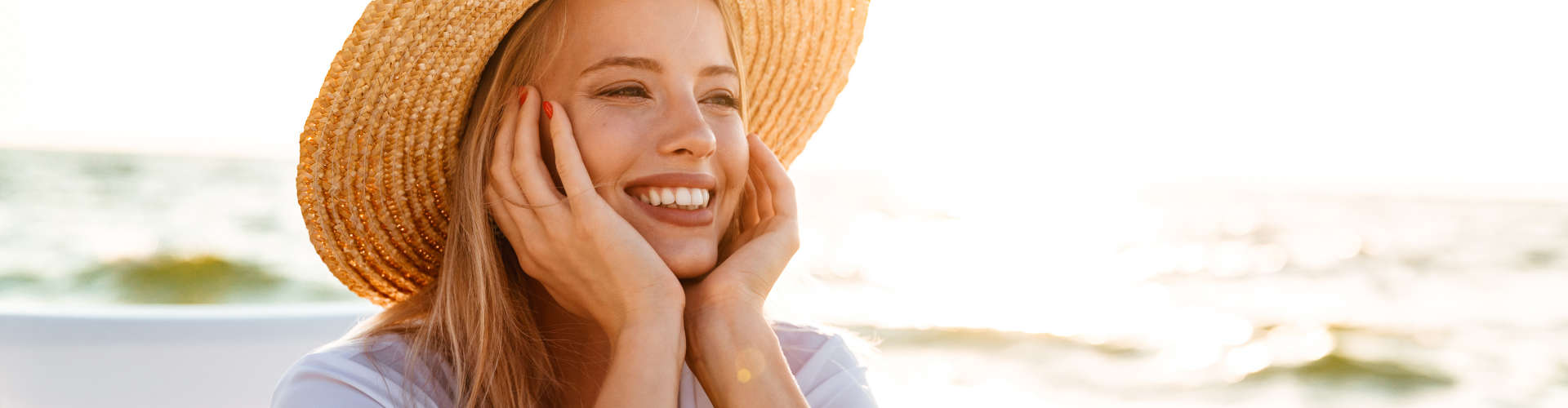 Cheerful woman 20s in straw hat smiling while sitting in lounge chair at seaside during summer morning.